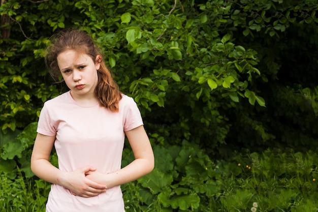 Onschuldig meisje houdt haar buik vast terwijl ze buikpijn heeft in het park Gratis Foto
