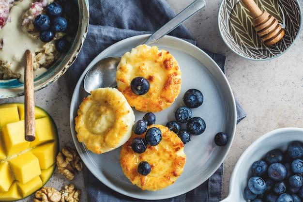 Ontbijt achtergrond. havermout, kwark pannenkoeken met bessen en fruit op donkere achtergrond. Premium Foto