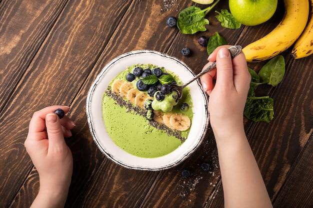 Ontbijt detox groene smoothie kom van banaan en spinazie op houten oppervlak Premium Foto