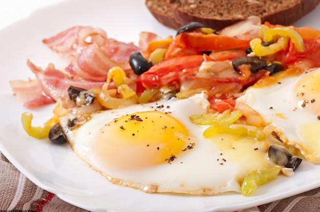 Ontbijt - gebakken eieren met spek, tomaten, olijven en plakjes kaas Gratis Foto