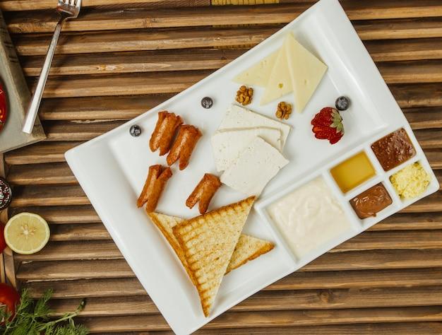 Ontbijt houten bord met pannenkoeken, honing, roomkaas, groenten en confituur in een vierkant wit bord Gratis Foto