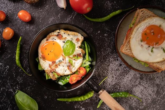 Ontbijt met gebakken eieren, worst en ham in een pan met tomaten. chili en basilicum Gratis Foto