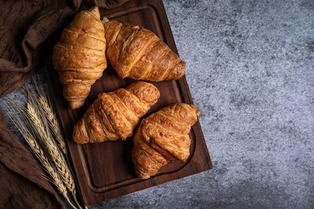 Ontbijt met verse croissants op houten bord Premium Foto