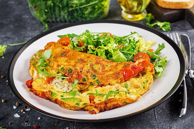 Ontbijt. omelet met tomaten, avocado, schimmelkaas en groene erwten op witte plaat. Premium Foto