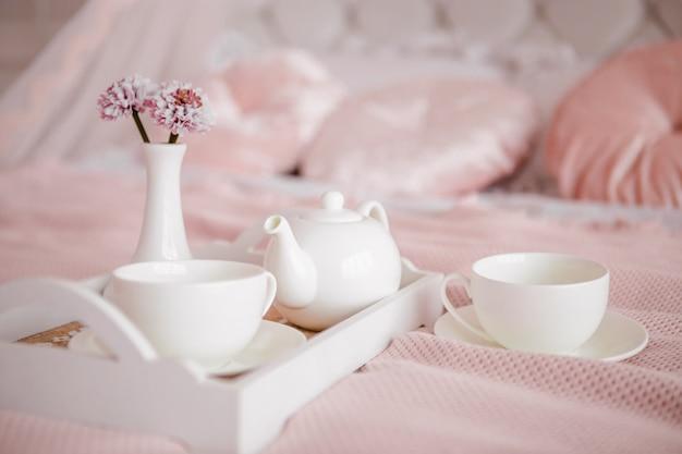 Ontbijt op bed met bloemen en witte kopjes. Premium Foto