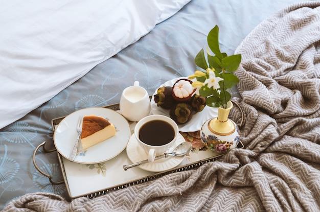 Ontbijt op bed plak van kaastaart en fruit met kop van koffie en bloem in een dienblad. Premium Foto