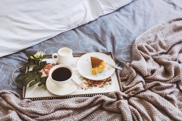 Ontbijt op bed segment van cheesescake met een kopje koffie en bloem in een lade. Premium Foto