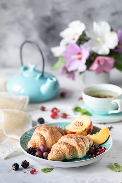 Ontbijt van verse bessen en fruit met croissants, thee een boeket van zomerbloemen. Premium Foto