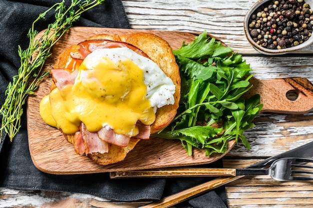 Ontbijtburger met bacon, egg benedict, hollandaise saus op briochebroodje Premium Foto