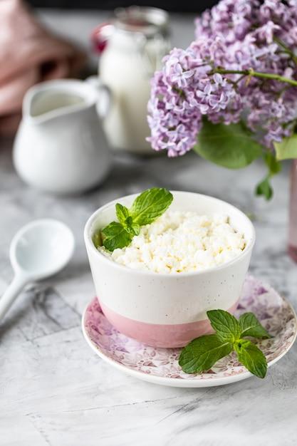 Ontbijtkwark met bosbessen, room, melk op een witte lijst en een tak van bloemen. Premium Foto
