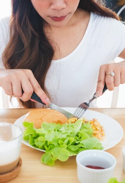 Ontbijtomelet, brood, hamburger en groenten eten op een witte plaat met behulp van een mes en vork Premium Foto