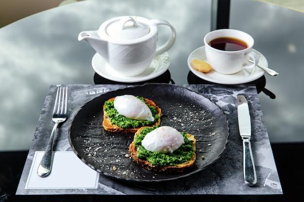 Ontbijttafel, geroosterd brood met gepocheerd ei en groenen Premium Foto