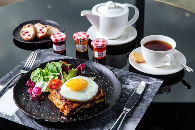 Ontbijttafel instelling, gebakken sandwich met salade en omelet Premium Foto