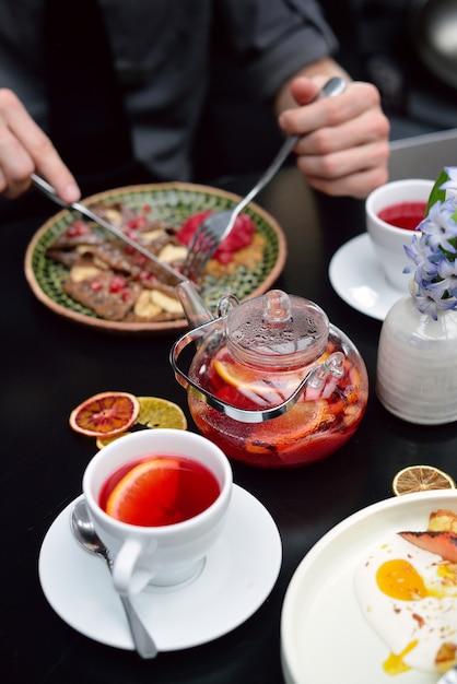 Ontbijttafel instelling met pannenkoeken, thee. stel eet Premium Foto