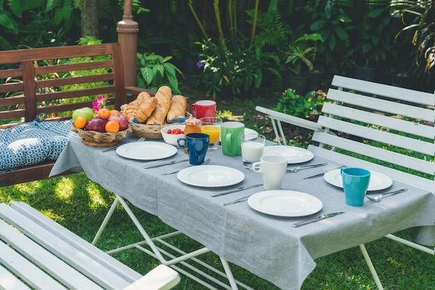 Ontbijttafel met eten in de tuin Premium Foto