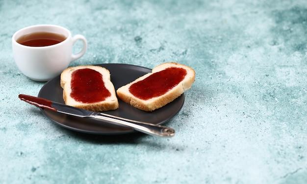Ontbijttoosts met aardbeijam in een zwarte plaat en een kop thee. Gratis Foto