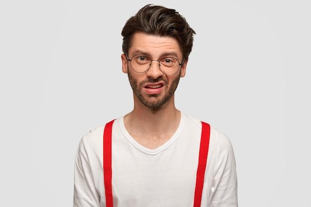 Ontevreden aantrekkelijke jonge mannelijke hipster heeft een verbaasde uitdrukking, fronst zijn gezicht, kijkt met afkeer, merkt iets onaangenaams op, draagt een wit overhemd met rode bretels. gezichtsuitdrukkingen concept. Gratis Foto