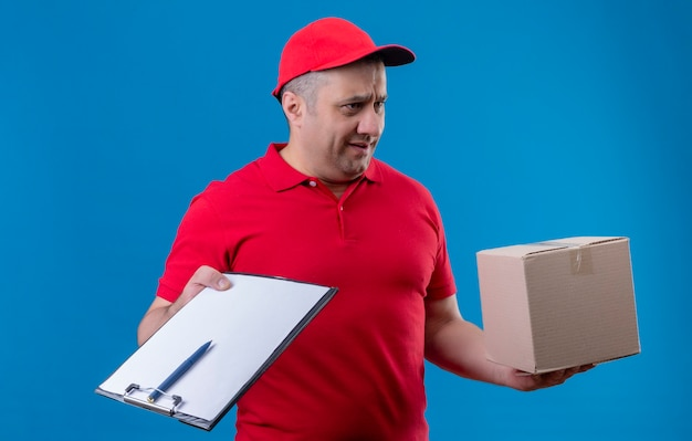 Ontevreden bezorger die een rood uniform draagt en een pet met een doos en een klembord die opzij kijkt met een fronsend gezicht dat over de blauwe ruimte staat Gratis Foto