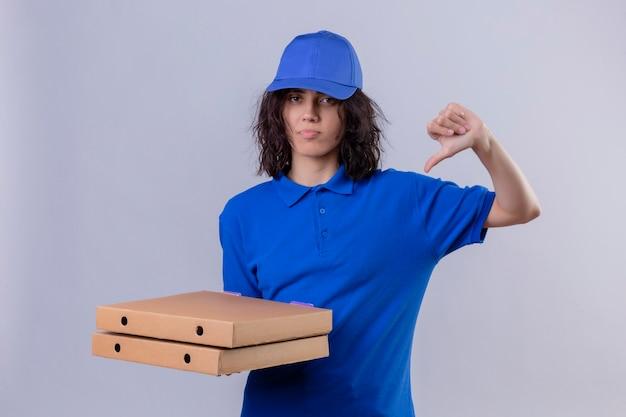Ontevreden bezorgmeisje in blauw uniform en pet met pizzadozen met duimen naar beneden staan Gratis Foto