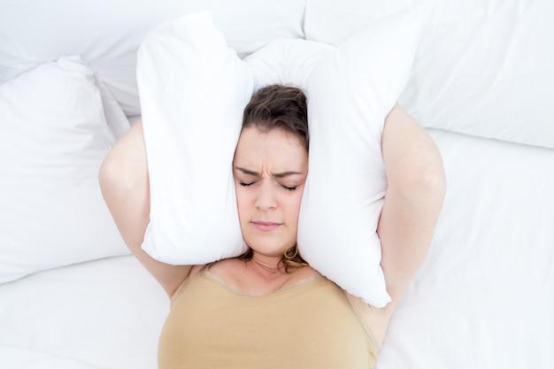 Ontevreden dame die oren met kussen in bed onderneemt Gratis Foto