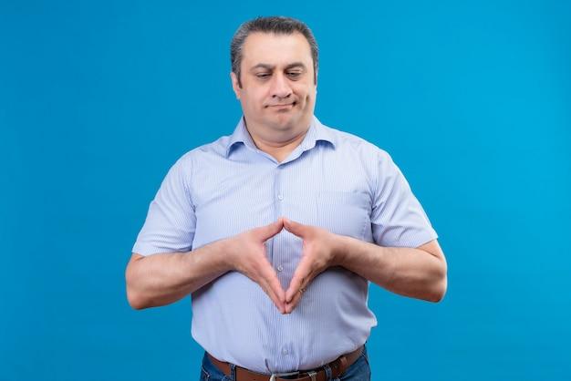 Ontevreden en verwarde man van middelbare leeftijd in blauw gestreept overhemd denken en hand in hand samen op een blauwe ruimte Gratis Foto