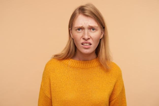 Ontevreden jonge langharige roodharige vrouw fronste ontevreden haar gezicht, gekleed in vrijetijdskleding terwijl ze poseerde op beige Gratis Foto