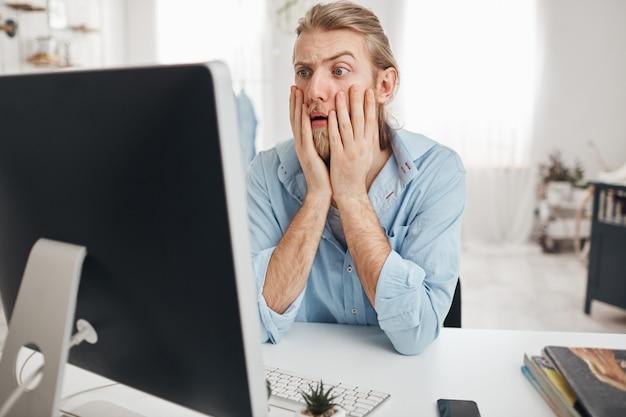 Ontevreden jonge mannelijke manager kijken met afgeluisterde ogen en verbazing, geschokt door financieel verslag, leunend op ellebogen zittend aan tafel voor computerscherm tijdens harde werkdag Gratis Foto