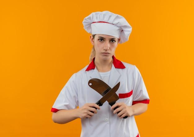 Ontevreden jonge mooie kok in uniform chef-kok gebaren nee met hakmes en mes op zoek geïsoleerd op oranje ruimte Gratis Foto