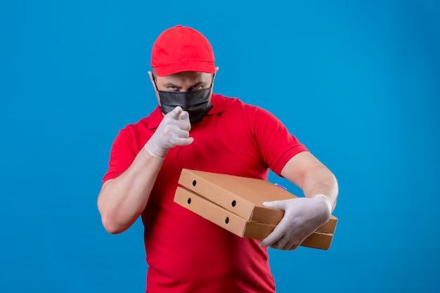 Ontevreden levering man dragen rode uniform en pet in gezicht beschermend masker houden pizzadozen wijzend met vinger met fronsend gezicht staande over blauwe chtergro Gratis Foto
