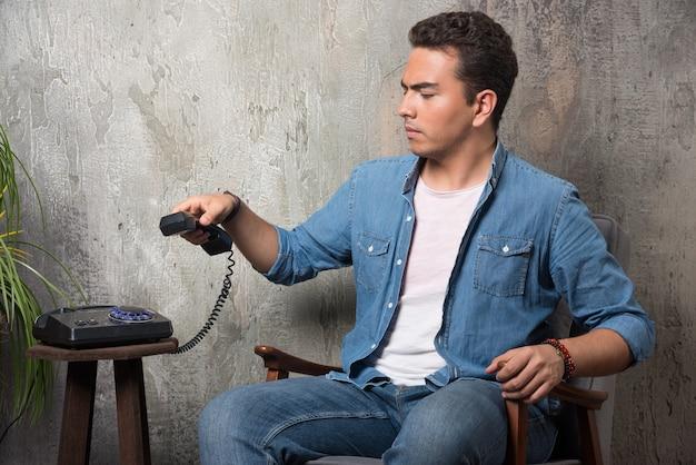 Ontevreden man met handset en zittend op een stoel. hoge kwaliteit foto Gratis Foto