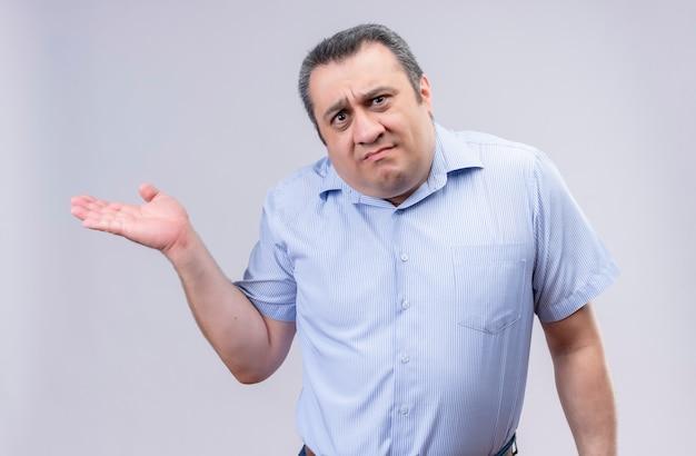 Ontevreden man van middelbare leeftijd met een blauw overhemd met verticale strepen die zijn hand spreidt terwijl hij staat Gratis Foto