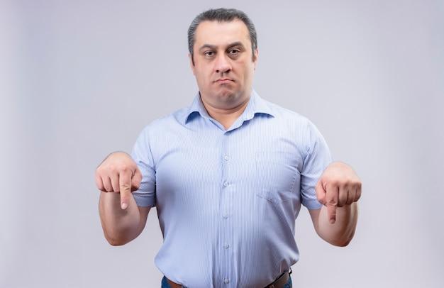Ontevreden man van middelbare leeftijd met een blauw verticaal gestript hemd met wijsvingers naar beneden terwijl hij staat Gratis Foto