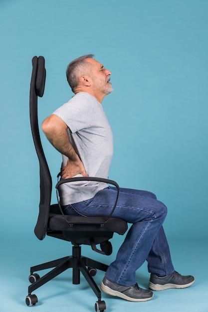 Ontevreden man zit in de stoel met rugpijn op blauwe achtergrond Gratis Foto