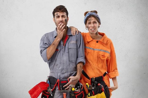 Ontevreden monteurs repareren kabellijnen, hebben vuile gezichten na hard werken Gratis Foto
