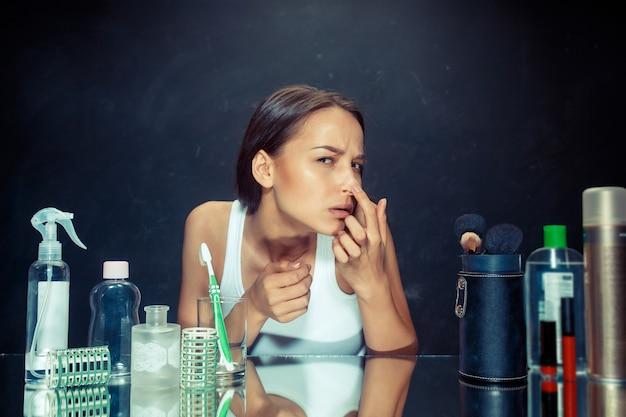Ontevreden ongelukkige jonge vrouw die haar zelf in spiegel op zwarte studioachtergrond bekijkt. roblem huid en acne concept. kaukasisch model in de studio Gratis Foto