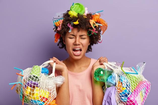 Ontevreden, stressvolle afro-amerikaanse vrouw houdt twee tassen vol vuilnis vast, huilt van negatieve emoties, is moe na het verzamelen van afval, bezorgd en verontrust over ecologische problemen Gratis Foto