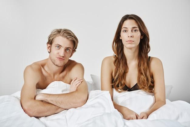 Ontevreden teleurgesteld paar zittend in bed onder deken ,, vriend kruist handen in verwarring twee getrouwde mensen verloren hun passie voor elkaar, dus hebben seksuele problemen in de slaapkamer Gratis Foto