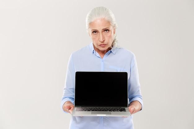 Ontevreden trieste vrouw met laptopcomputer met een leeg scherm Gratis Foto