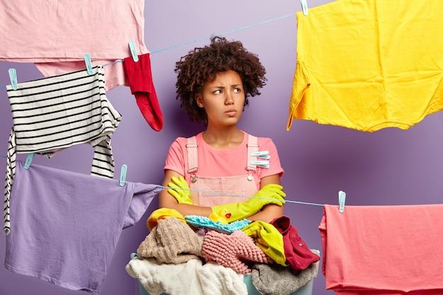 Ontevreden, vermoeide huisvrouw draait haar gezicht om, staat met gevouwen armen in de buurt van een wasbak met wasgoed, bezig met het wassen van kleren thuis, waslijnen in de buurt met schone was, doet klusjes in huis. Gratis Foto