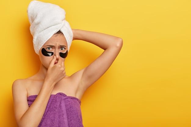 Ontevreden vrouw bedekt neus, fronst gezicht van onaangename geur, heeft zweterige huid, moet een bad nemen, in handdoek gewikkeld, maakt de huid voller Gratis Foto