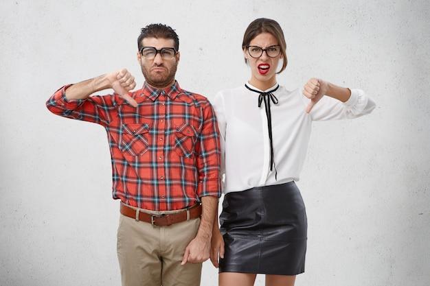 Ontevreden vrouw en man houden duimen naar beneden, keuren iets af, fronsen gezichten Gratis Foto