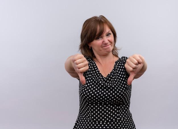 Ontevreden vrouw op middelbare leeftijd die duimen neerzet - op geïsoleerde witte achtergrond Gratis Foto