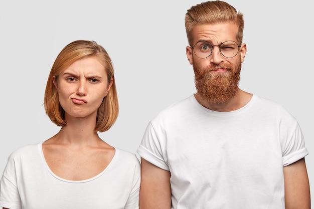 Ontevreden vrouwelijke en mannelijke collega's tuiten lippen en fronsende gezichten, houden niet van hun plan om de financiële situatie te verbeteren, dragen casual t-shirts, staan naast elkaar, geïsoleerd over een witte muur Gratis Foto