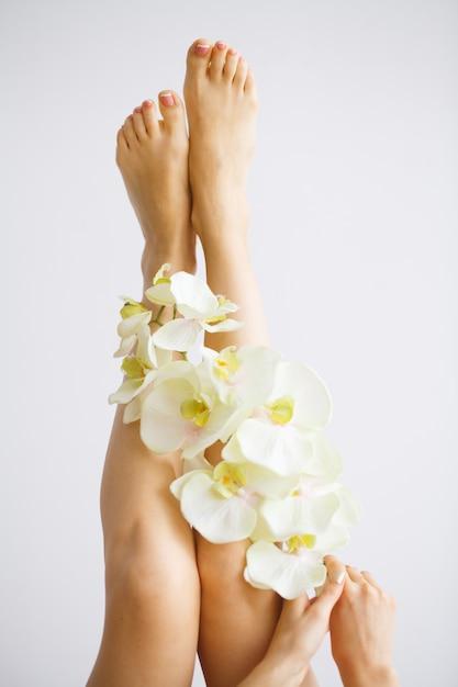 Ontharing. sluit omhoog vrouwenhanden wat betreft lange benen, zachte huid Premium Foto