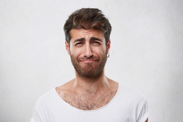 Ontmoedigde man met kapsel en baard die zijn wenkbrauwen fronst en spijt heeft van wat hij heeft gedaan. bedroefd man in wit t-shirt. mensen, mode, levensstijl, emoties concept Gratis Foto