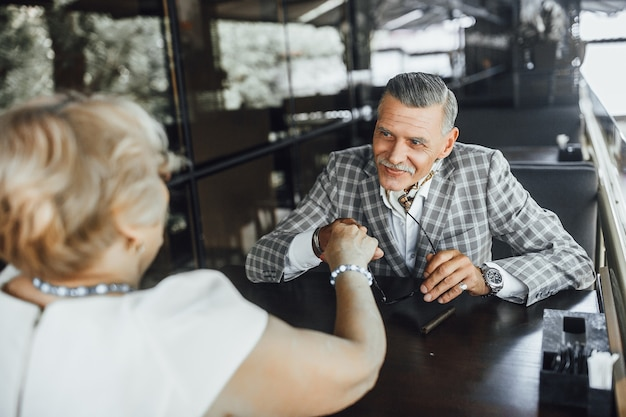 Ontmoet twee verliefde senioren, ze zitten op het zomerterras en kijken elkaar aan, ze leeft met hem mee Premium Foto