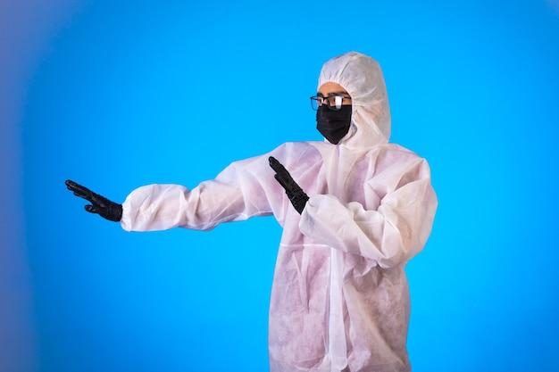 Ontsmettingsmiddel in speciaal preventief uniform stop gevaar dat van links op blauw komt. Gratis Foto