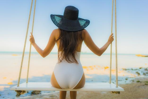 Ontspan de portret mooie jonge aziatische vrouwenzitting op de schommeling rond strand overzeese oceaan voor Gratis Foto