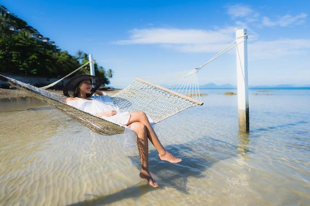 Ontspan de portret mooie jonge aziatische vrouwenzitting op hangmat rond overzeese strandoceaan voor Gratis Foto