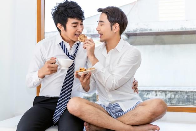 Ontspan en theetijd. portret van aziatisch homoseksueel paar dat koekje eet en geniet van grappig moment Premium Foto